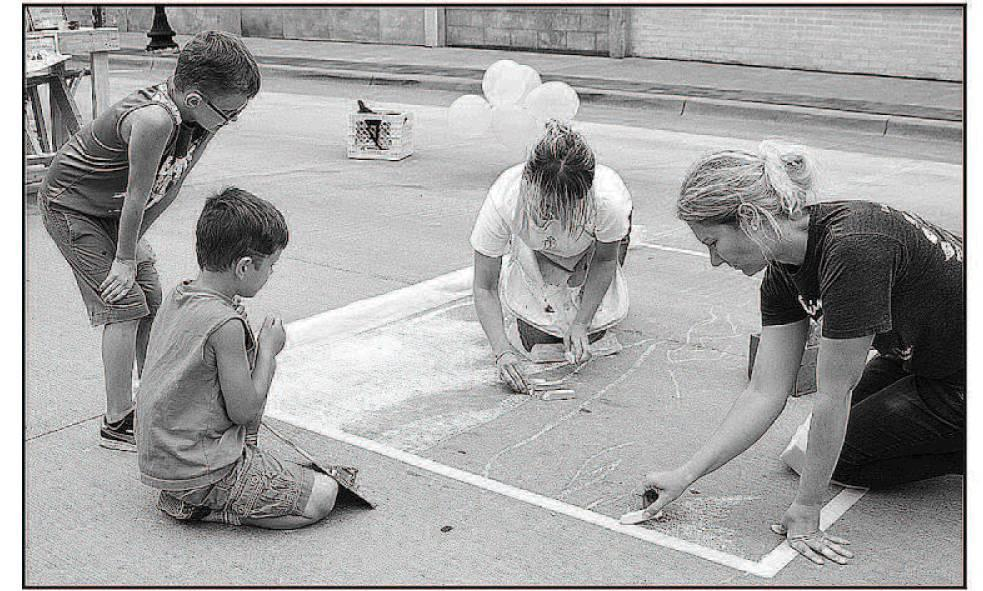 Catrina Wilson and Kelsey Adams create during the Milla palooza chalk art challen ge.