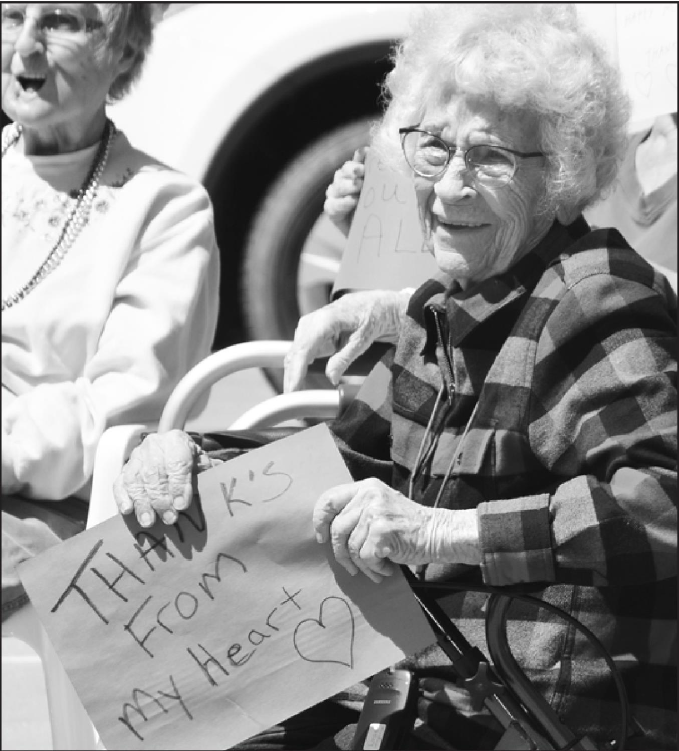 Photos by Sharon Sahlfeld Great Granddaughter Autumn Sneath (above left) provides a message for her Great Grandma Lorna Jones (above) during Tuesday's Hilltop Lodge Drive-By-Party Parade. Grandma returns her appreciation with a smile and a message of he