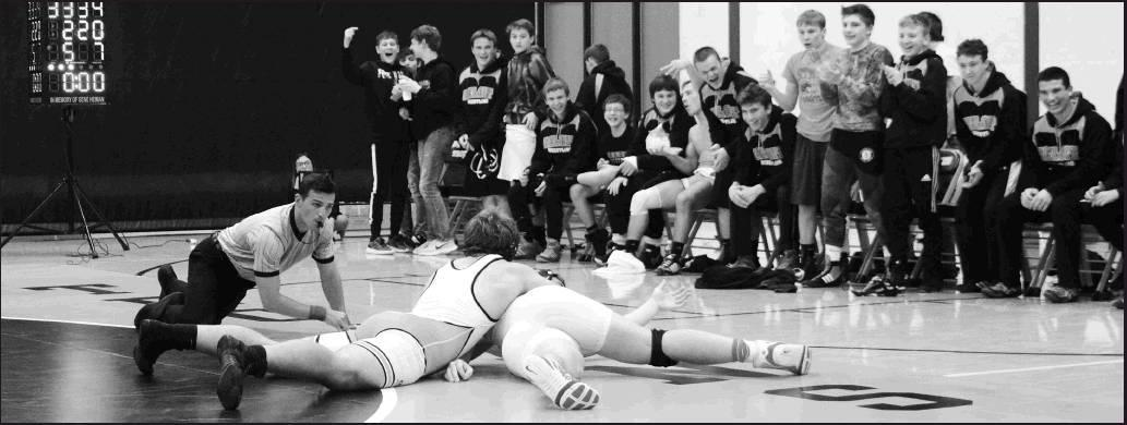 Sharon Sahlfeld photos          The Beloit Wrestling team cheer on junior Creighton Johnson during his 220 weight division defeat over Ryan Junkermier, 10-5. Beloit opened their season at home on Friday with two dual wins over Plainville and Phillipsbur