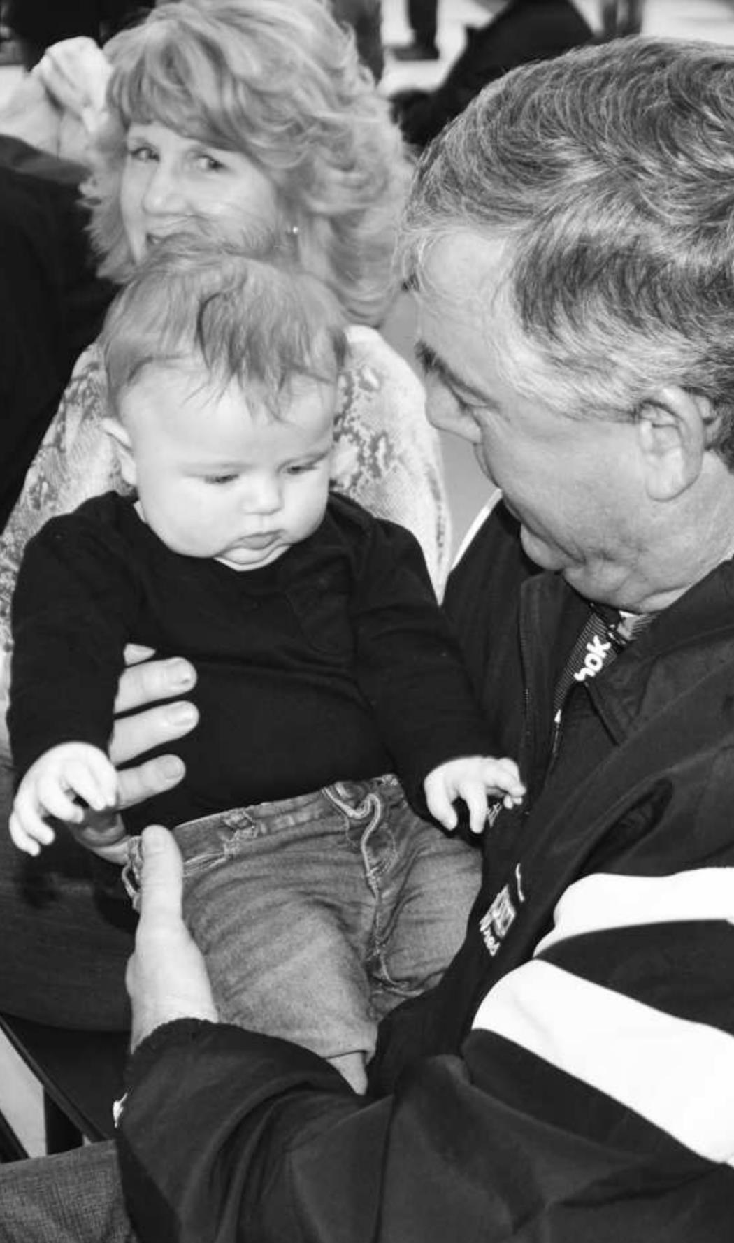 Mark and Marne Hewitt enjoy grandbaby Neva Josephine, during the halftime of the Beloit ladies basketball game.