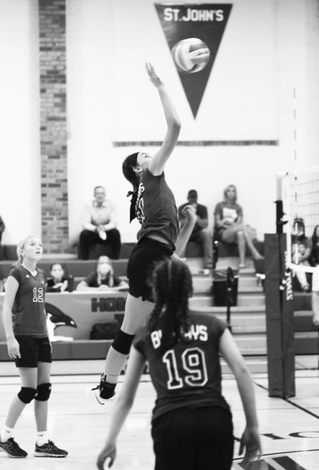 Sophia Thompson No. 17 attacks the at the net for the St. John's/Tipton middle school kill while teammates Carlie Brummer No. 12 and Clare Meyer No. 19 are ready on the play. Andrea Wiles courtesy photo