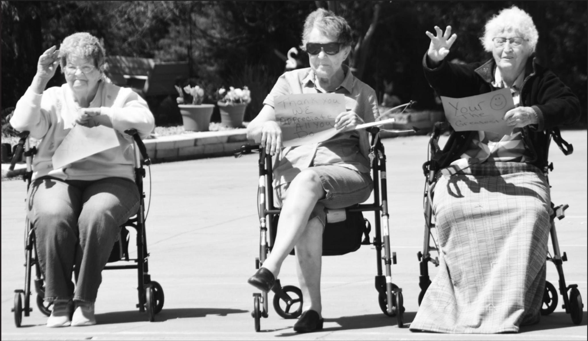 From left to right: Charlotte Hanson, Dolores Obermueller and Alvera Long provide waves and signs of appreciation to drive-by parade attendees during the Hilltop Lodge parade event on Tuesday.