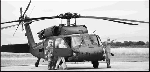 Pilot Greg Shirley (far right), Daryl Hawkins (boarding) and Crew Chief Blare Noel prepare for their continued flight to Salina. Sharon Sahlfeld photos