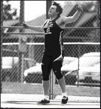 "Colin Chandler watches it fly in the shot put with a distance of 53'2.25"" for a regional championships and state mark."