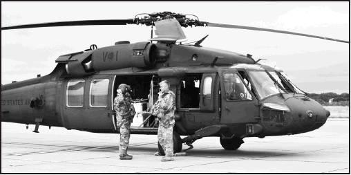 Pilot Jason Wilson and Crew Chief Jesse Johnson put on their flying gear in flight preparation.