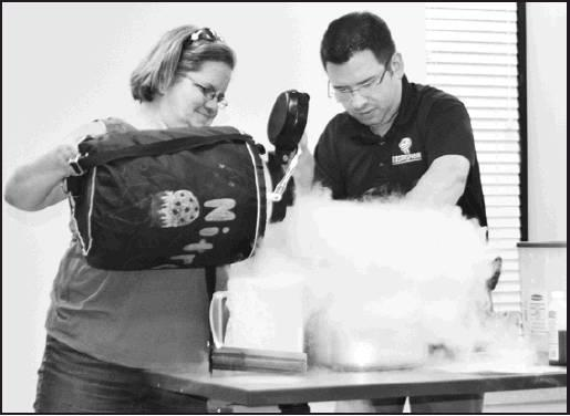 "Port Library Program Director Terry Peterson helps Caleb Gimar as she pours liquid oxygen into the mixture to create ice cream for the attendees at the Hutchinson Cosmosphere ""Living in Space"" presentation at the Port Library on Tuesday."